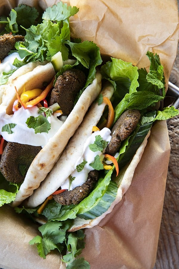 Top view of falafel in flatbread with pickled vegetables, lettuce, yogurt, cilantro, on brown paper.