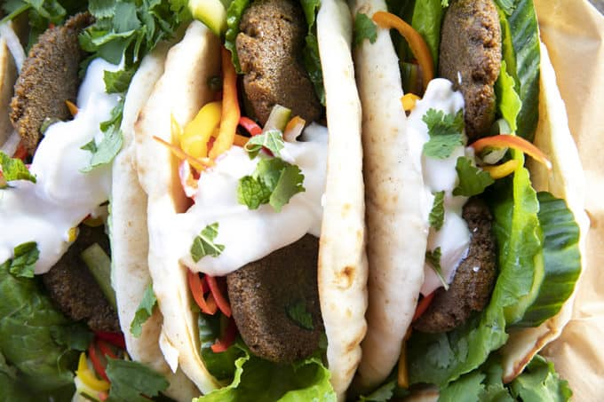 Falafel in flat bread with yogurt, pickled vegetables, lettuce, and cilantro.