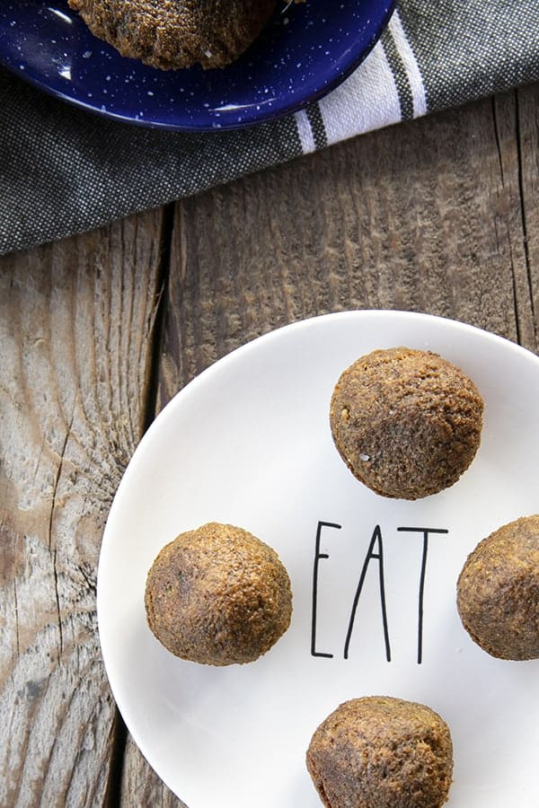 "falafel balls on a plate that says ""eat"" and a wooden table"