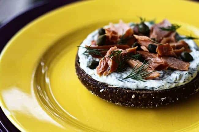Lemon Dill Spreadable Cream Cheese on a black Russian bagel with smoked salmon and capers from Foodie with Family.