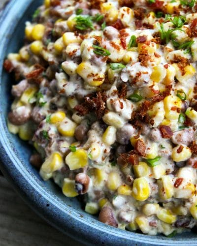 Slow-Cooker Black-Eyed Pea Dip with Corn and Bacon in blue speckled pottery bowl, sliced green onions, crumbled bacon, black eyed peas, corn, in a creamy sauce