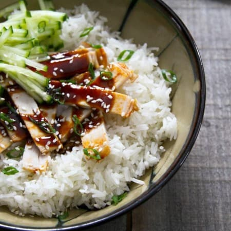 Strips of slow-cooker korean style barbecue pork with sauce on rice with cucumbers in taupe ceramic bowl with a black rim, on wood background.