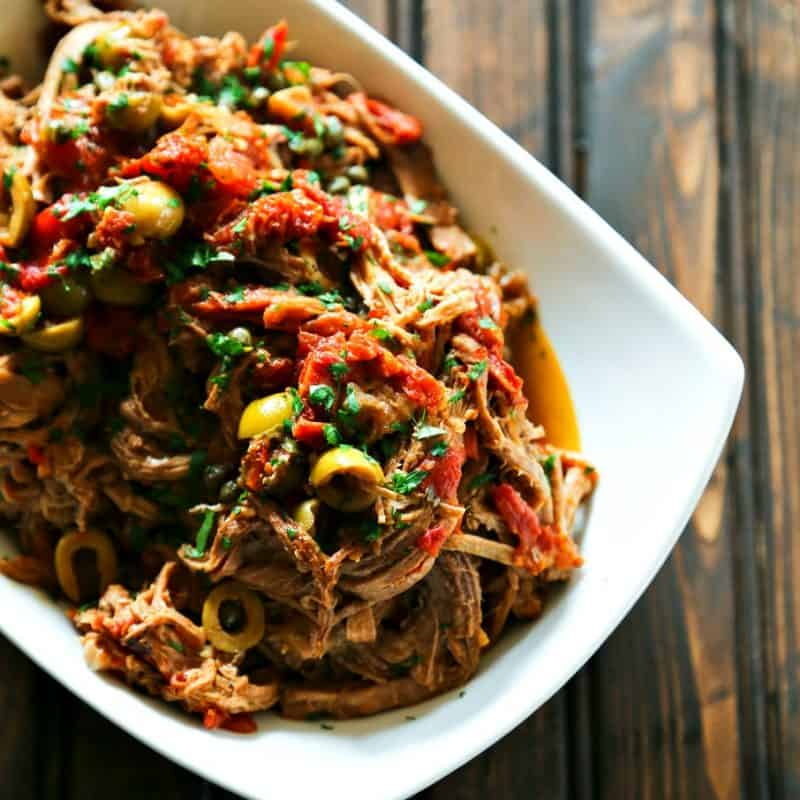 Slow Cooker Italian Shredded Beef full of sun dried tomatoes, wine, garlic, fire roasted tomatoes, olives, and capers from foodiewithfamily.com