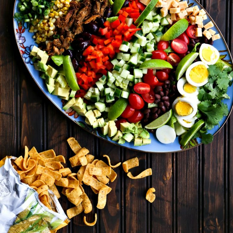 STex-Mex Cobb Salad is crispy romaine absolutely bursting with green onions, roasted corn, crispy carnitas, bell peppers, cucumbers, tomatoes, hard boiled eggs, avocados, and lime juice. This is a serious and seriously fun salad!