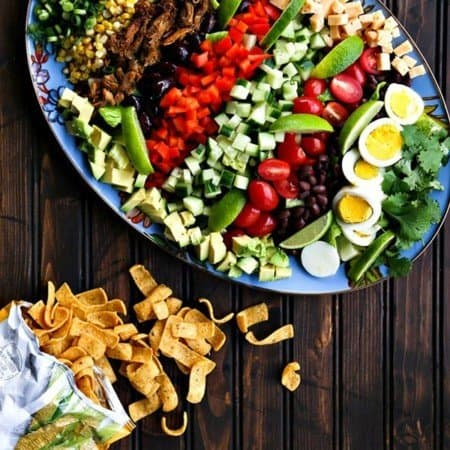 Square crop Tex-Mex Cobb Salad on blue floral Mackenzie Childds platter, open bag of fritos, dark wood table, greens, corn, cucumbers, black beans, hard boiled eggs, carnitas, cherry tomatoes, red bell peppers, blackk olives, cubed cheese, avocados.