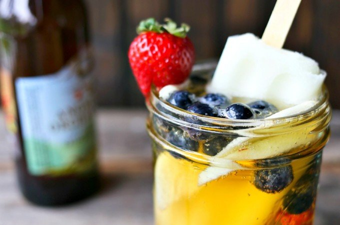 Hard Cider Sangria-by-the-Glass is fresh fruits soaked in crisp hard cider with a lime ice pop stir stick.