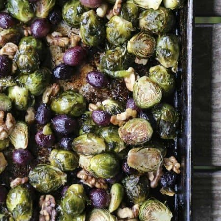 Roasted Brussels Sprouts with Walnuts and Grapes on antique metal sheet pan, wooden table, maldon sea salt