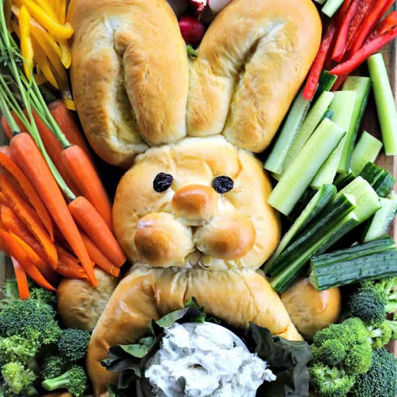 bread shaped like bunny, surrounded by raw cucumbers, bell peppers, broccoli, radishes, and carrots with their stems attached, belly of bread bunny lined with lettuce leaves and filled with dip