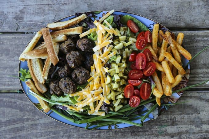 Cheeseburger Salad from foodiewithfamily.com with sesame bun croutons. grilled meatballs and green onions, cheese, pickles, tomatoes, and hot fries.