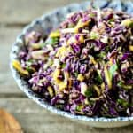 Spicy Mango Slaw is crunchy purple cabbage with a hint of tropical sweetness from just barely ripe mango, and the tart and tangy lime juice and honey dressing gets a flavour boost from minced red onion and fragrant cilantro.