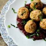 Turkey and stuffing meatballs, cranberry sauce, white target plate on antique blue and white scallopped plate, wooden background, 3/4 view, chopped parsley and green onions