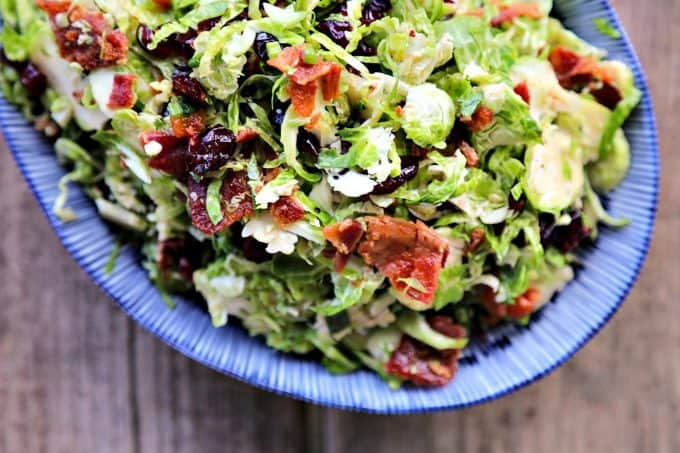 Cranberry Brussels Salad with Bacon Vinaigrette: shredded brussels sprouts, crisp bacon, dried cranberries, craisins, blue and white oval serving bowl, wooden background