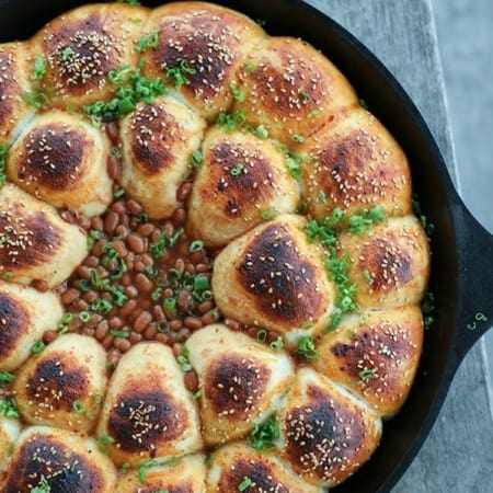Cheeseburger Bombs Baked Bean Skillet, sesame topped rolls stuffed with meatballs, arranged in circles around baked beans, cast iron skillet, sliced green onions