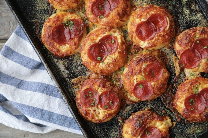 Pepperoni Pizza Bialys Recipe: fresh-from-the-oven, chewy, bagel-like bread topped with chopped garlic, the barest hint of pizza sauce and olive oil, a generous cap of melted cheese, and a couple of crispy-edged pepperoni to crown it.
