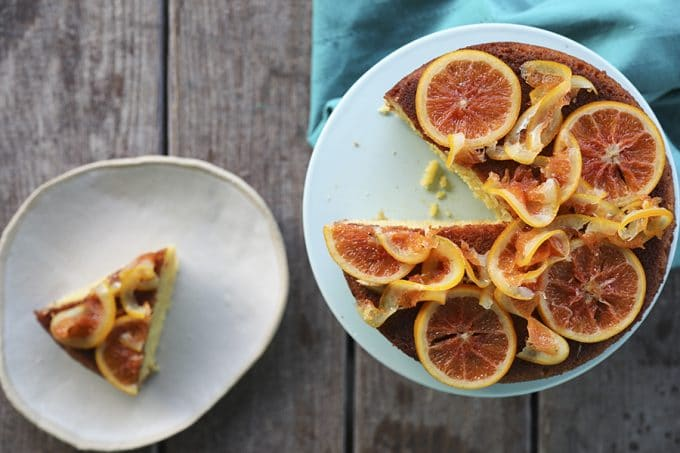 Orange Olive Oil Cake with Candied Oranges is light, has a fine crumb, is perfectly moist but not sopping, is beautifully fragrant of oranges, has just a hint of warm cardamom, and is festooned with thin slices of orange lovingly candied in honey and cardamom syrup.