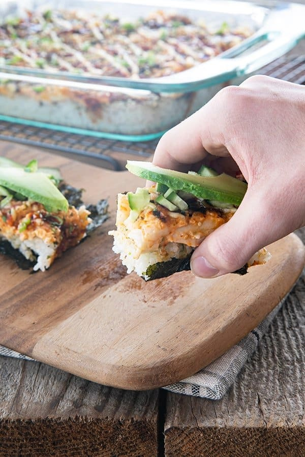sushi bake on nori with cucumbers and avocado being lifted