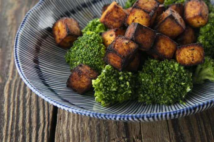 Crispy, golden brown cubes of air fryer tofu served with a drizzle of honey and broccoli on a blue and white striped oblong bowl.
