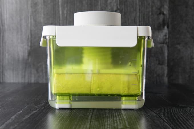 Tofu being pressed in a green, plastic, transparent tofu press.