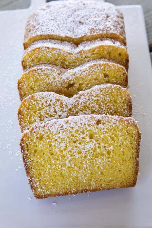 Sliced loaf of French Grandma Lemon Yogurt Cake dusted with powdered sugar on a white plate.