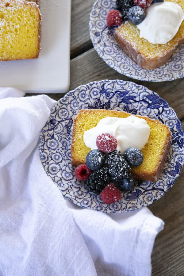 French Grandma lemon yogurt cake with berries, powdered sugar, and yogurt on a blue and white plate with a white linen.