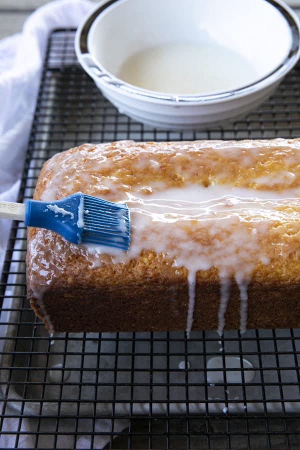 Glazing a French Grandma Lemon Yogurt Cake on a black cooling rack over a pan.