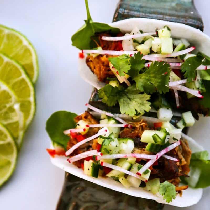 Jicama Tacos with carnitas, cucumber onion salsa, radishes, and cilantro.