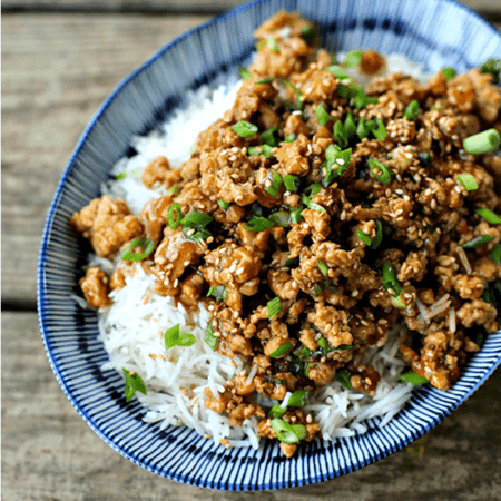 Cheater Sesame Chicken ground chicken in sweet and spicy sauce, sesame seeds, sliced green onions, long grain white rice, asian bamboo pattern blue and white bowl on wooden bench