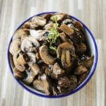 blue edged, white ceramic bowl, wooden tile background, simple garlic butter sauteed mushrooms, sprig of fresh thyme