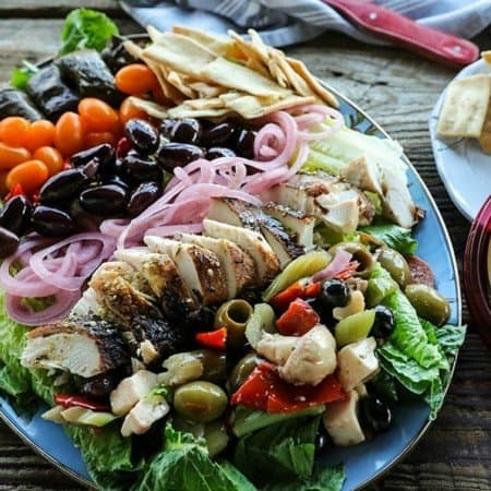 Greek Salad with lemon garlic chicken, marinated olive salad, quick pickled red onions, crumbled feta cheese, garlic stuffed kalamata olives, tiny grape tomatoes, stuffed grape leaves, Greek salad dressing, pita chips as croutons, and a hearty dollop of hummus. This salad will fill you up with sunshiny goodness without making you feel like a slug. The post includes instructions on how to pack these salads up to four days ahead of time for work-week and school lunches.