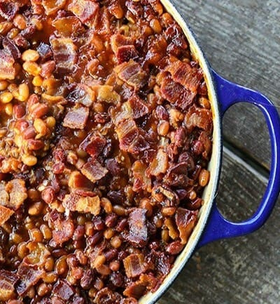 Le Creuset cobalt blue braiser, baked beans, crispy bacon, barbecue sauce, wooden bench