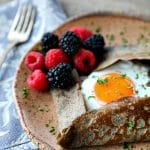 Buckwheat Crepe with fried egg, ham, and cheese on a pottery plate that looks like wood, fresh blackberries, parsley garnish