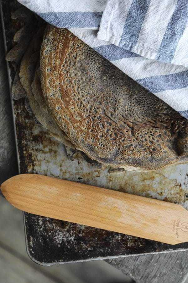 Pure buckwheat crepes on an antique cookie sheet under a blue and white towel, wooden crepe turner