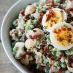 bacon pea pasta salad in white bowl with hard boiled eggs, bacon bits, rustic wood table