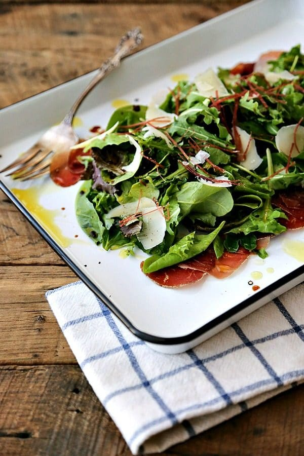 Bresaola Parmesan Salad on white quarter sheet pan with cobalt blue rim, blue and white tea towel, antique fork, rustic wood tabletop