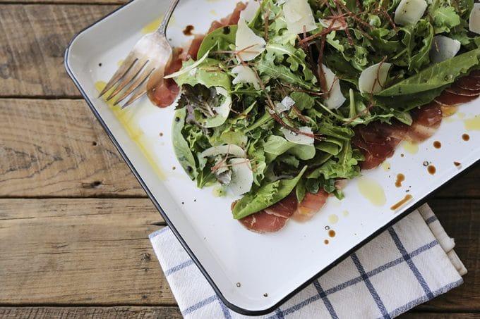 Bresaola Parmesan Salad on white quarter sheet pan with cobalt blue rim, blue and white tea towel, antique fork, rustic wood tabletop