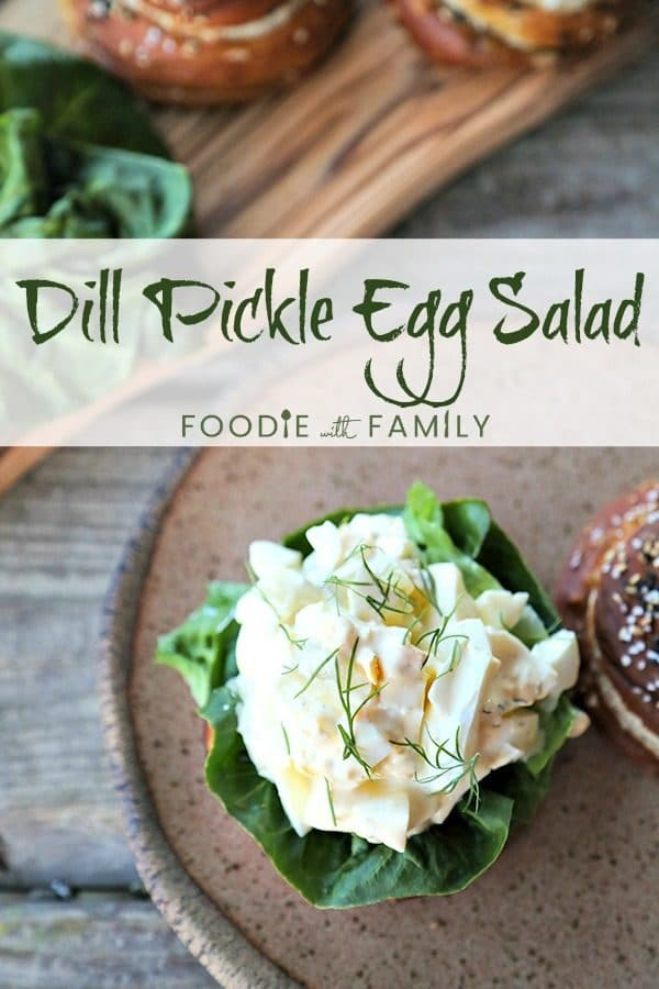 Dill Pickle Egg Salad with fresh dill on lettuce and soft pretzel roll, speckled brown pottery plate with rough edge, wooden cutting board with rolls and lettuce, rustic wooden table.