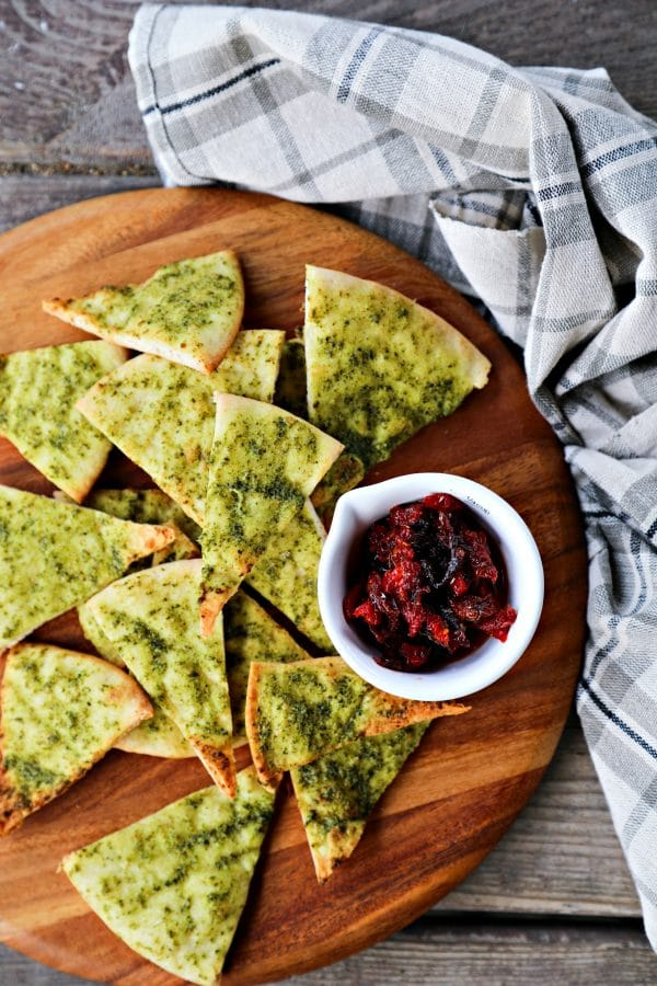 Crispy, crunchy, perfect pesto brushed homemade pita chips are as easy as cut, brush, bake and make a great snack or salad accompaniment.