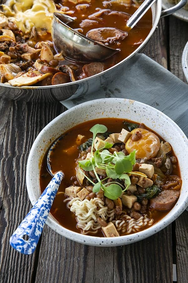 Korean Army Stew or Budae Jjigae in a white bowl with an egg yolk and a blue enamel spoon.