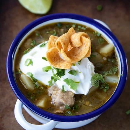 PORK GREEN CHILI IN A WHITE ENAMEL BOWL WITH A BLUE RIM AND HANDLES