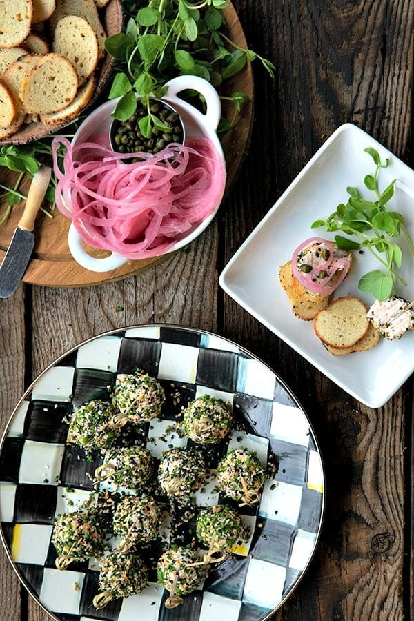 These gorgeous little two-bite, miniature cheese balls are dressed up with smoked salmon, chives, and everything bagel seasoning and taste like New York City when served with bagel chips, pickled red onions, and capers.